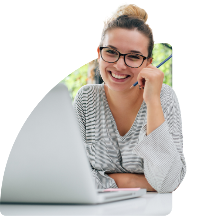A women wearing glasses, smiling, in front of a laptop.