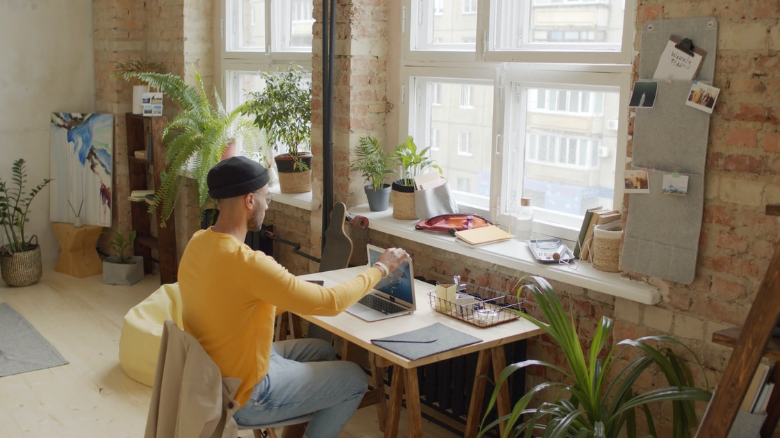 A man writing in a laptop. He's seated in a table in front of windows. His room has many plants.