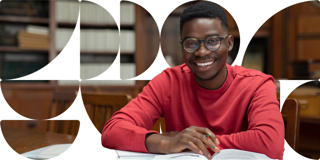 A young black man smiling, he has open books on a table and a pencil in his hand